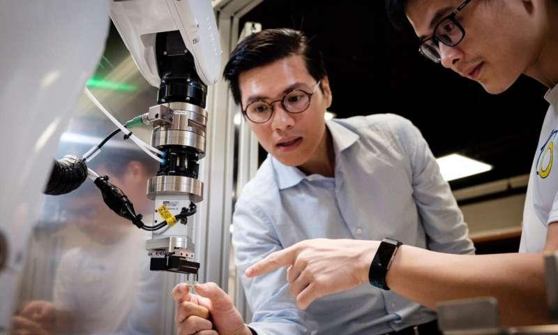 TS. Phạm Quang Cường (trái) thảo luận về robot Archimedes cùng TS. Phạm Tiến Hùng, kỹ sư trưởng trong cùng nhóm nghiên cứu. Nguồn: NTU Singapore