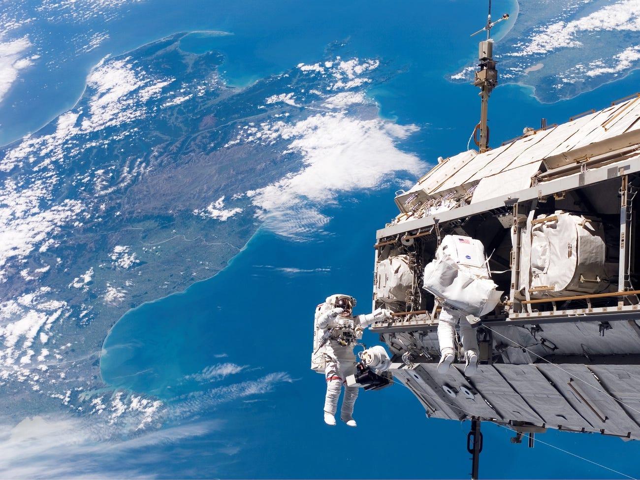 Các nhà du hành vũ trụ Robert L. Curbeam Jr., Christer Fuglesang tham gia một hoạt động ở ngoài tàu vũ trụ, phía dưới là New Zealand và eo biển Cook ở châu Á Thái bình dương. Nguồn: NASA.