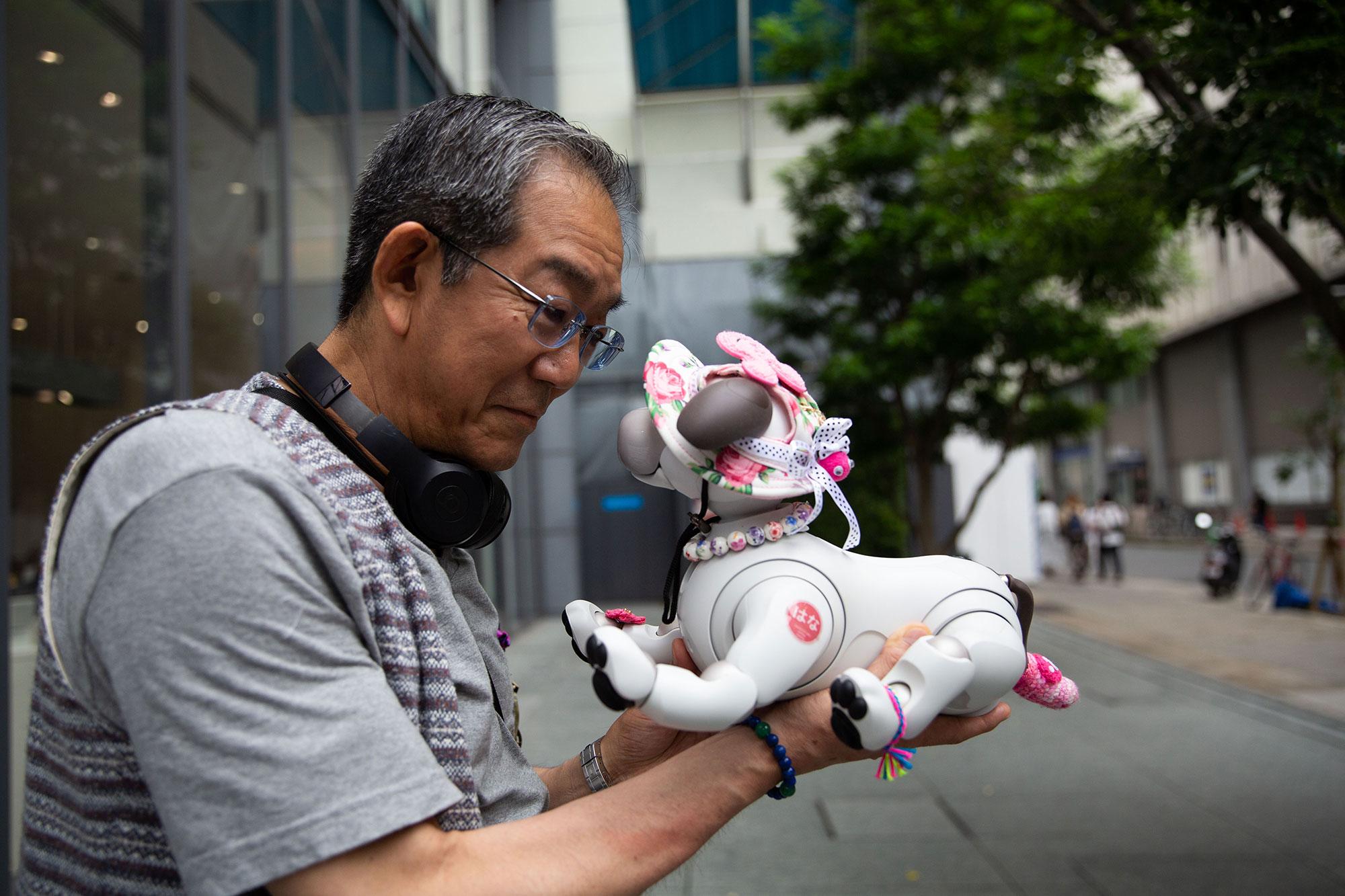 Một người đàn ông cao tuổi và chú Aibo của mình bên ngoài cửa tiệm. Ảnh