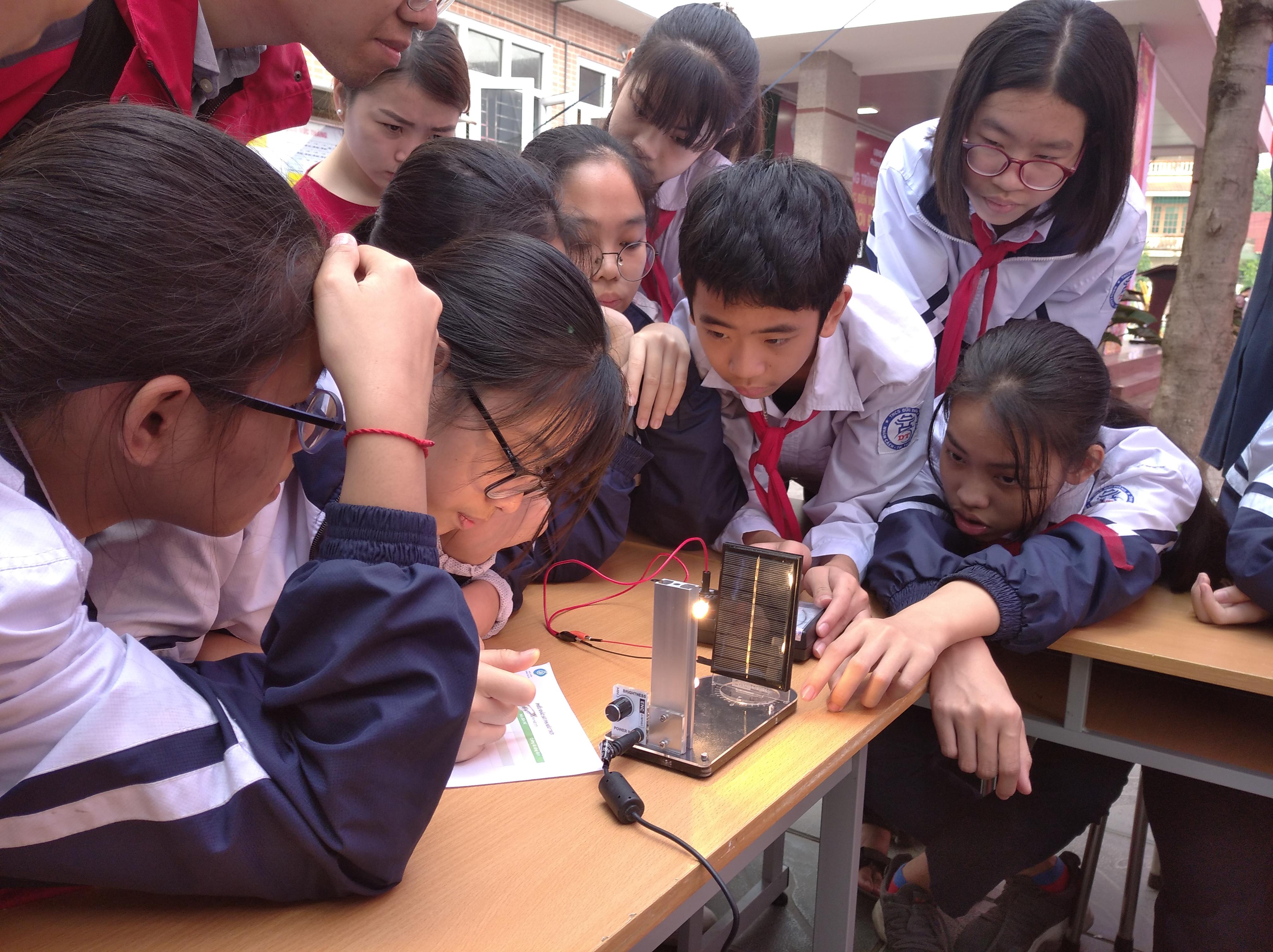 """Tại trạm """"Năng lượng"""", cô giáo trao đổi về cách khai thác các nguồn năng lượng hiện nay và hướng dẫn học sinh sử dụng máy đo điện năng của tấm pin mặt trời khi có ánh sáng chiếu vào ở các góc 0, 30, 60, 90 độ. Các bạn đã khám phá rằng dàn năng lượng mặt trời đạt công suất tối đa khi đặt vuông góc với ánh sáng."""