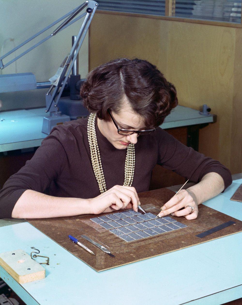 Một phụ nữ đang xâu các bộ phận của bộ nhớ trên máy tính Apollo Guidance Computer. Ảnh: Wikimedia Commons.