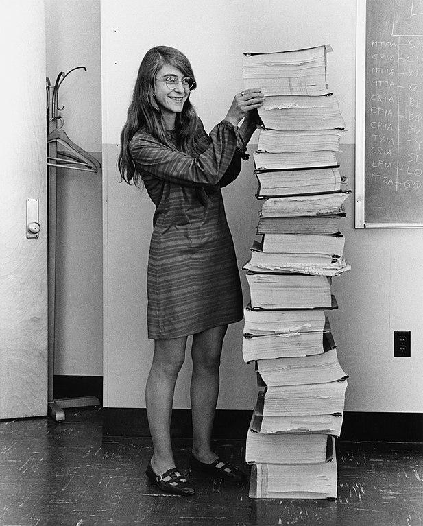 Margaret Hamilton đứng bên chồng giấy ghi lại đoạn mã của phần mềm điều hướng mà nhóm của bà tại MIT đã phát triển cho chương trình Apollo. Ảnh: Wikimedia Commons.