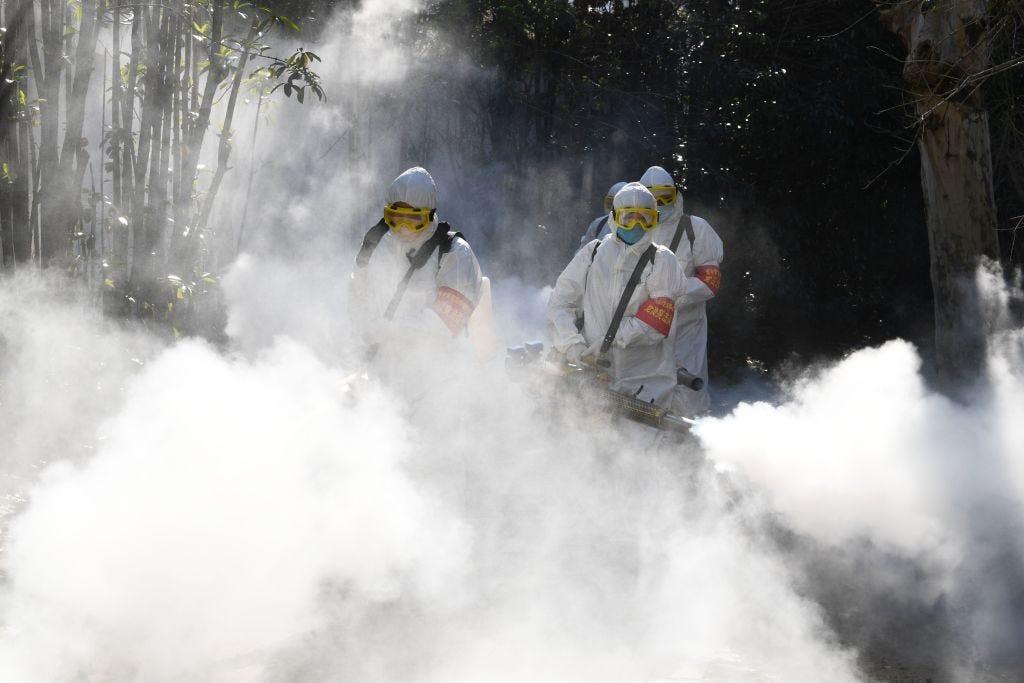 Các nhân viên phun thuốc khử trùng để phòng dịch Covid-19 tại Trung Quốc. Ảnh: Business Insider.
