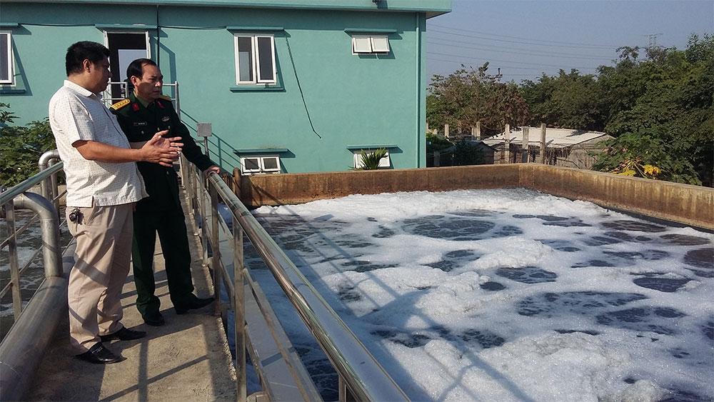 Đại tá Thiều Quốc Hân (bên trái) kiểm tra quá trình xử lý nước thải bằng công nghệ nano tại trạm xử lý nước thải tập trung cụm công nghiệp Quất Động (huyện Thường Tín, TP Hà Nội).