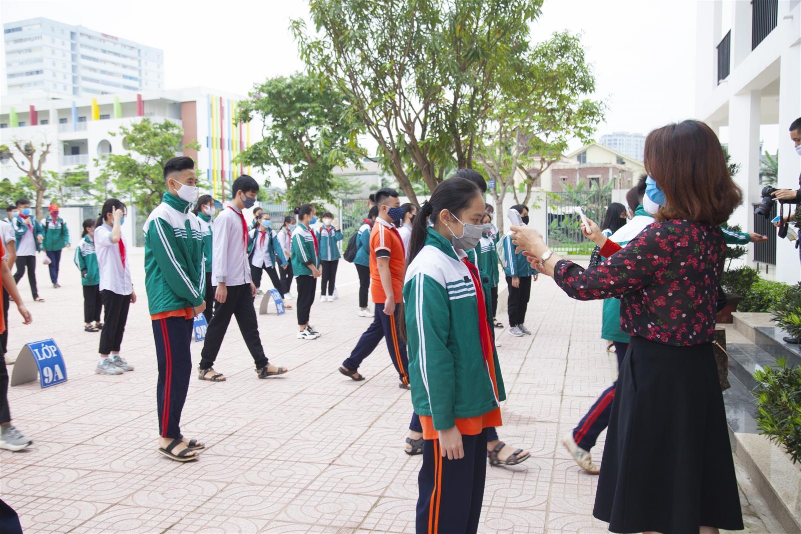 Học sinh Trường THCS Hưng Bình (TP Vinh, Nghệ An) đo thân nhiệt trước khi vào lớp. Ảnh: giaoducthoidai.vn
