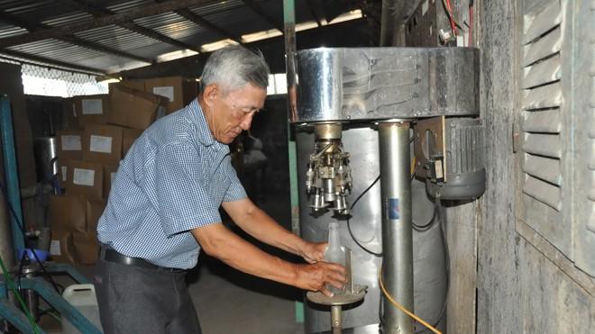 Ông Nguyễn Phú Tia đóng nút chai bằng máy. Ảnh: Tiền Phong.
