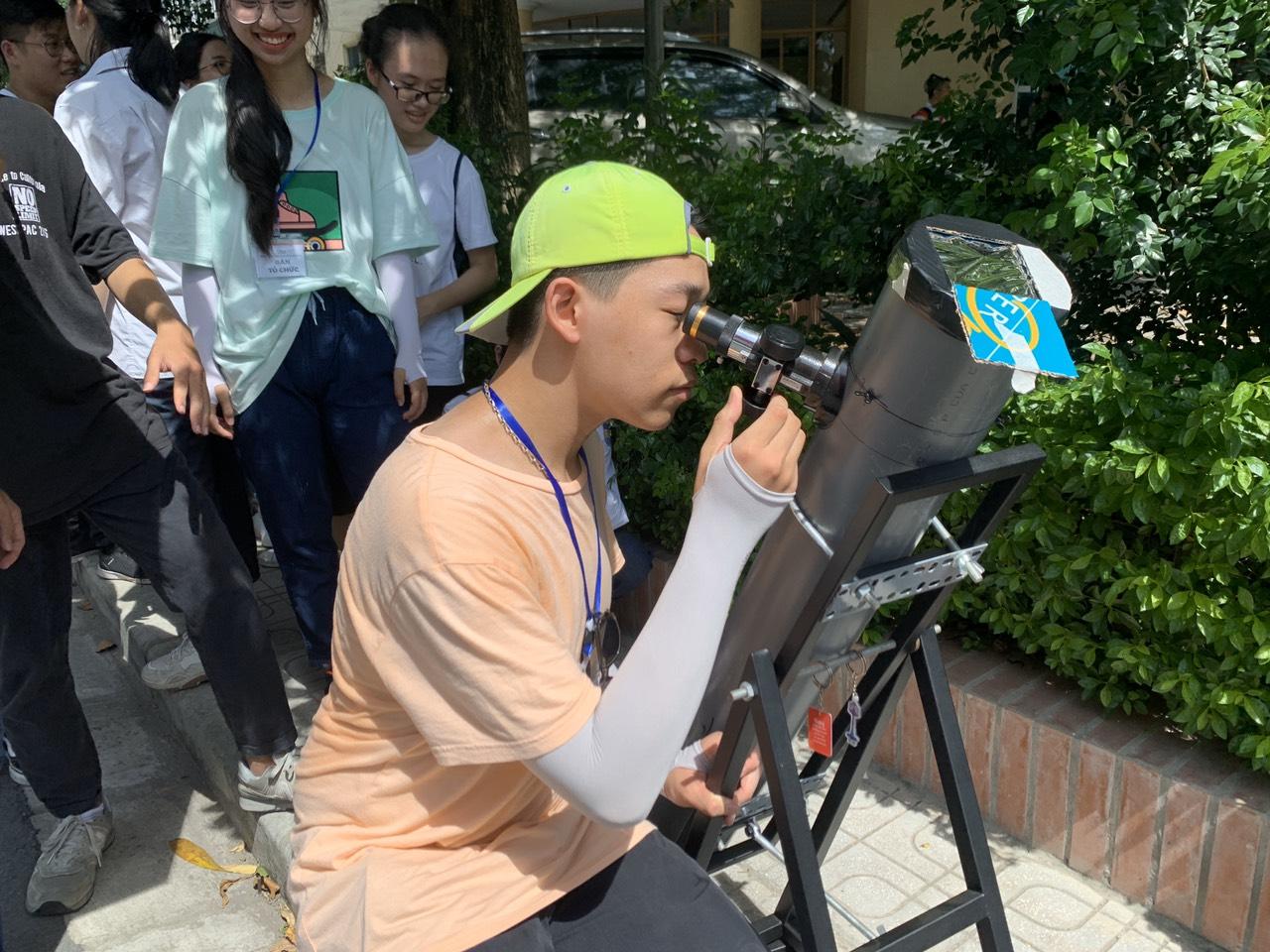 Em Dương Phan Anh - Học sinh lớp 11 chuyên Lý,THPT Chu Văn An đang quan sát nhật thực bằng kính thiên văn phản xạ tự chế.