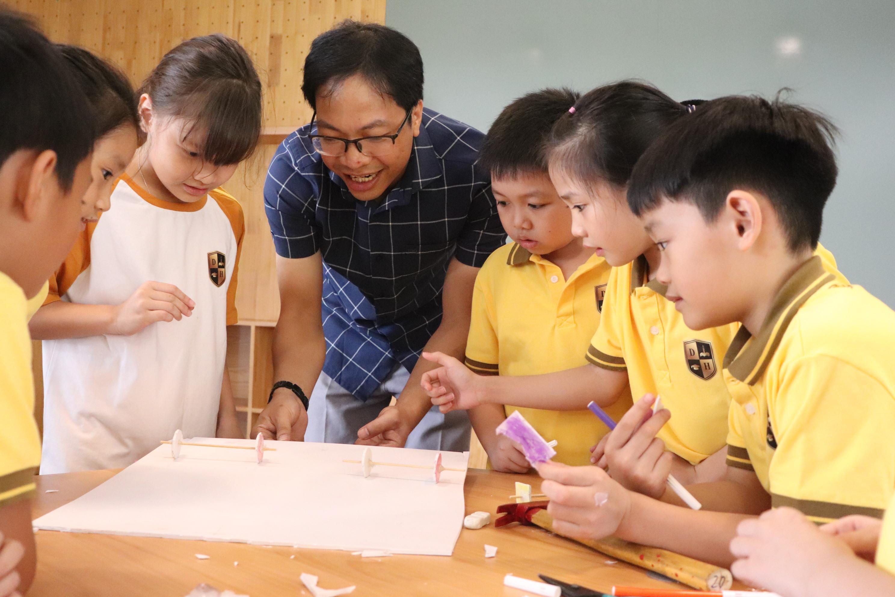 Thầy Hà Văn Lanh và các học sinh lớp 3 Trường tiểu học Dạ Hợp, TP Hòa Bình, trong giờ học về lực cản trong chuyển động. Ảnh: HTL