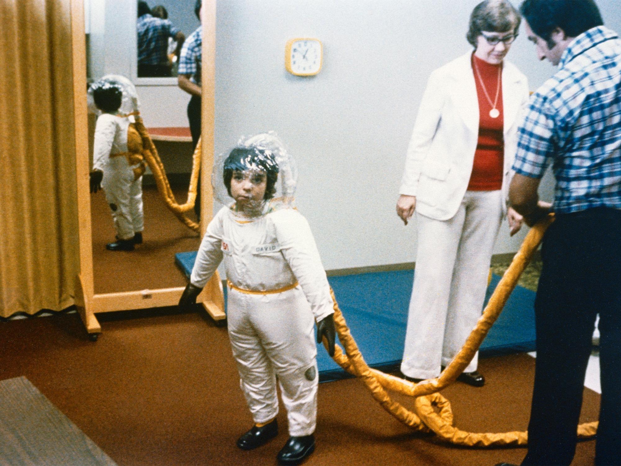 """David Vetter, người được nhớ đến với biệt danh """"cậu bé bong bóng"""" sống cả đời trong bộ đồ bảo vệ và bong bóng nhựa trong suốt vì mắc SCID, chứng bệnh rối loạn miễn dịch di truyền. Ảnh: NASA/JSC."""