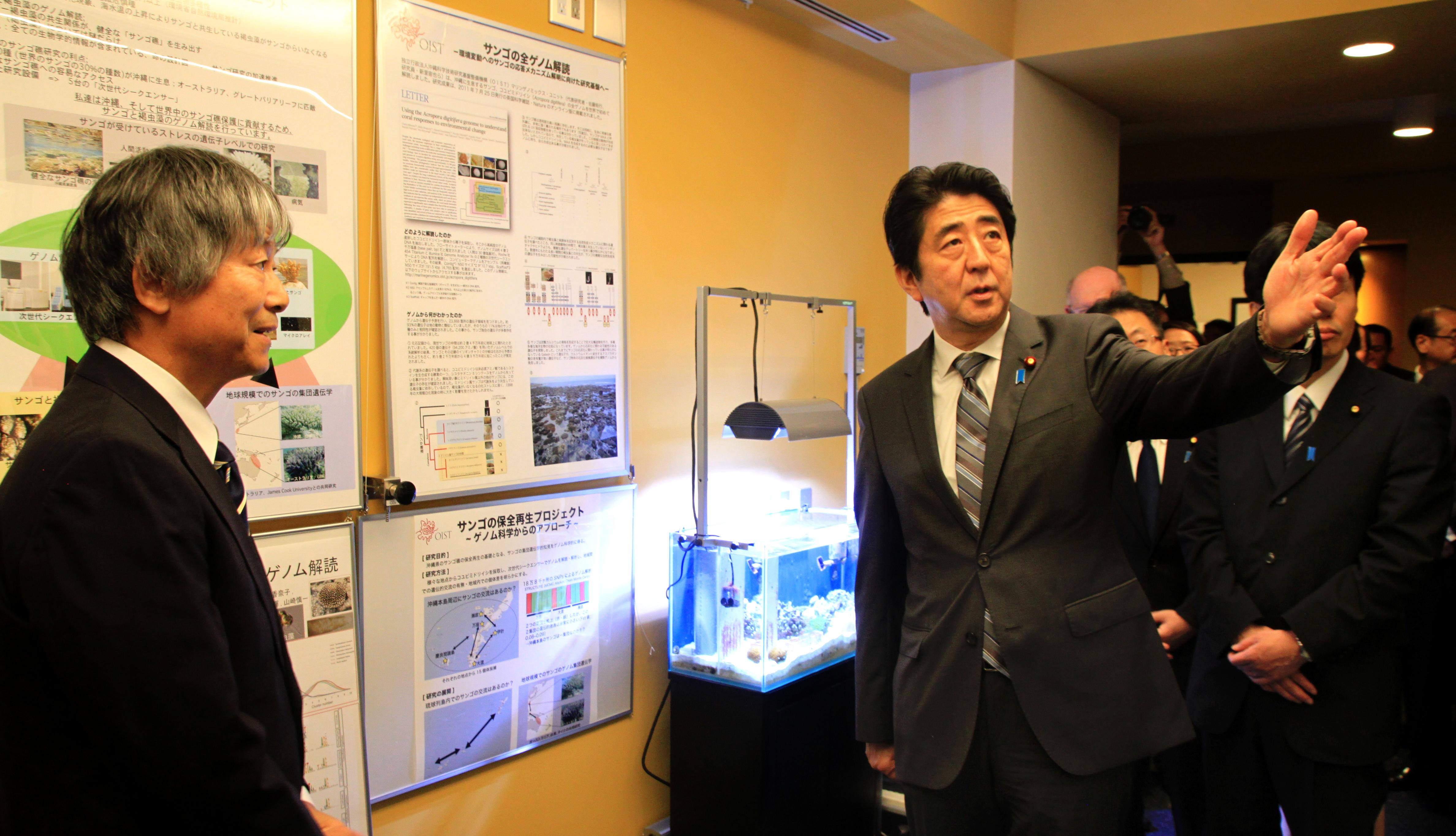 Thủ tướng Shinzo Abe trao đổi với giáo sư hệ gene Noriyuki Satoh trong chuyến tới thăm Viện KH&CN Okinawa năm 2013. Nguồn: Viện KH&CN Okinawa