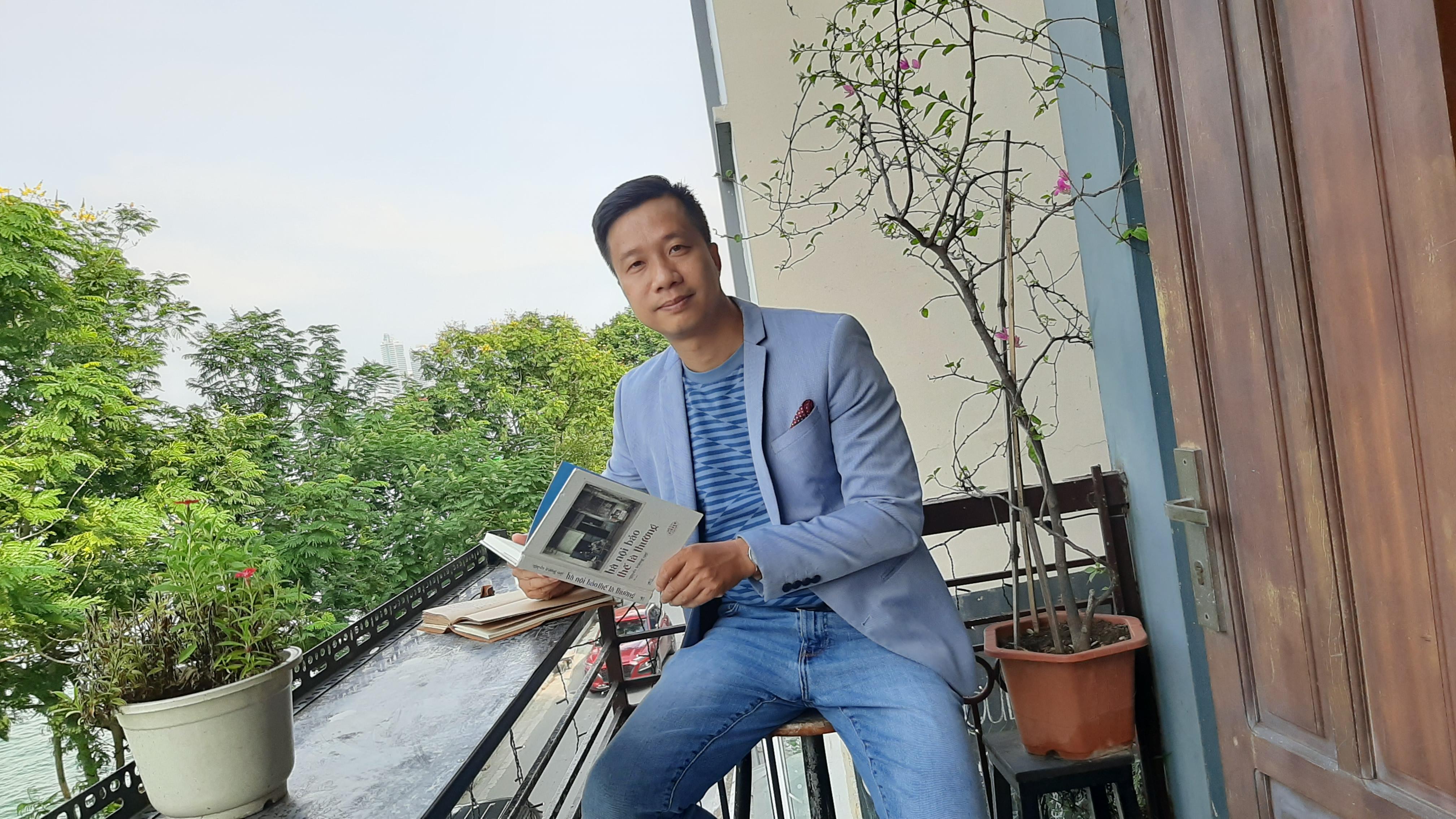 Tác giả Nguyễn Trương Quý bên tác phẩm mới ra mắt – Hà Nội bảo thế là thường. Ảnh: NVCC