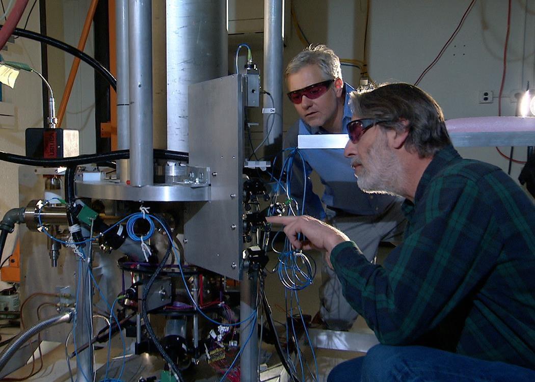 Hai nhà vật lý của NIST là Steve Jefferts (bên phải) và Tom Heavner với đồng hồ hạt nhân NIST-F2, một tiêu chuẩn về thời gian dân sự mới của Mĩ. Nguồn: nbcnews.com