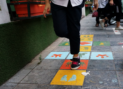 Trẻ em thích thú với những hình khối trò chơi dân gian được tạo ra trên đường đến trường