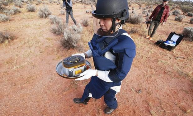 Một thành viên của Cơ quan Thám hiểm Hàng không Vũ trụ Nhật Bản (JAXA) thu mẫu vật tiểu hành tinh do Hayabusa2 thả về ở Úc. Ảnh: theguardian