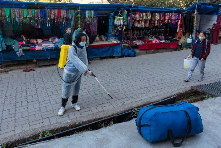 Phun thuốc khử trùng trên hè phố ở Dharmsala, Ấn độ.