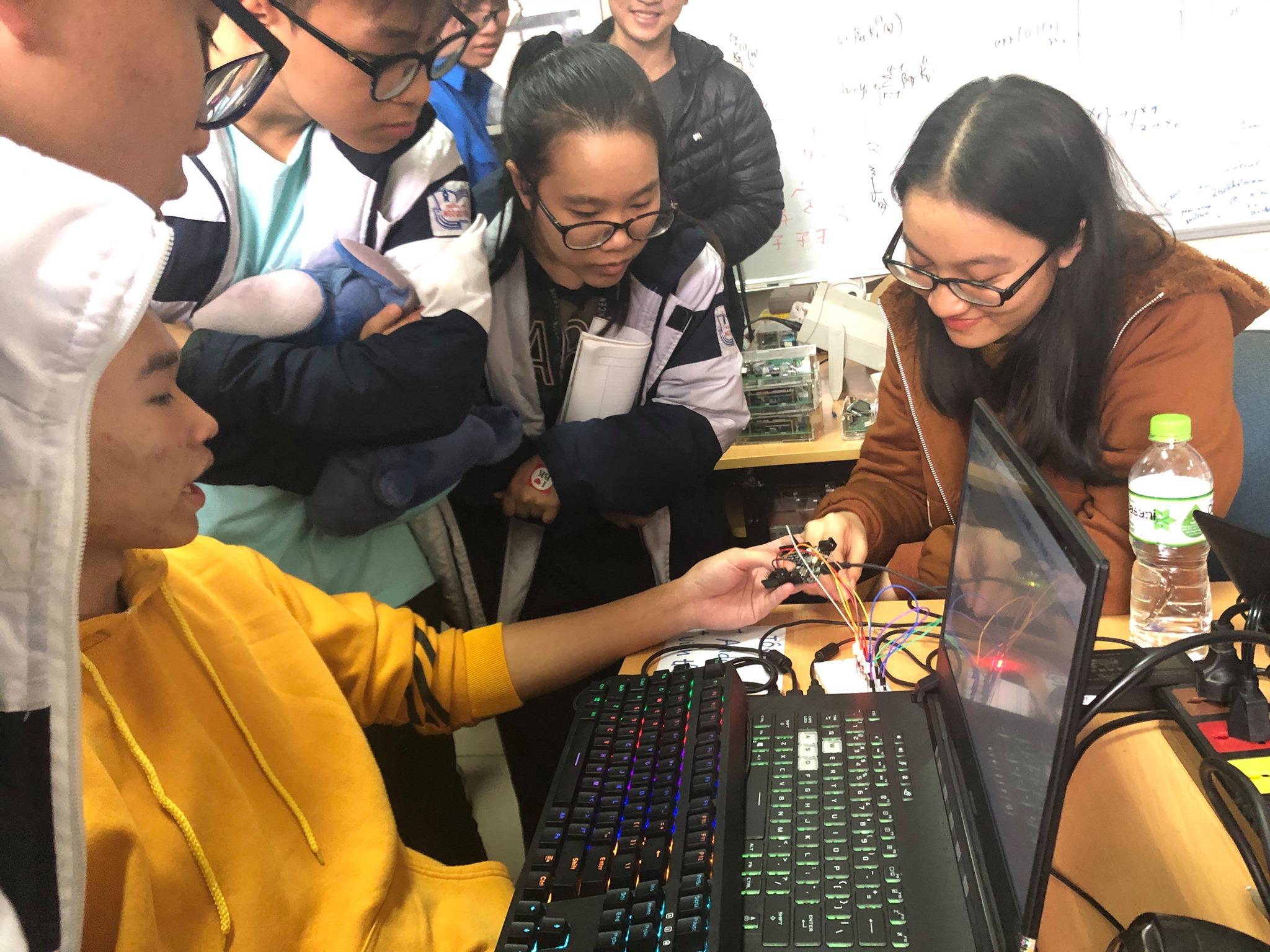 Sinh viên hướng dẫn kỹ thuật cho các bạn học sinh về cấu phần cơ bản của linh kiện điện tử và lập trình. Ảnh: Air SENSE