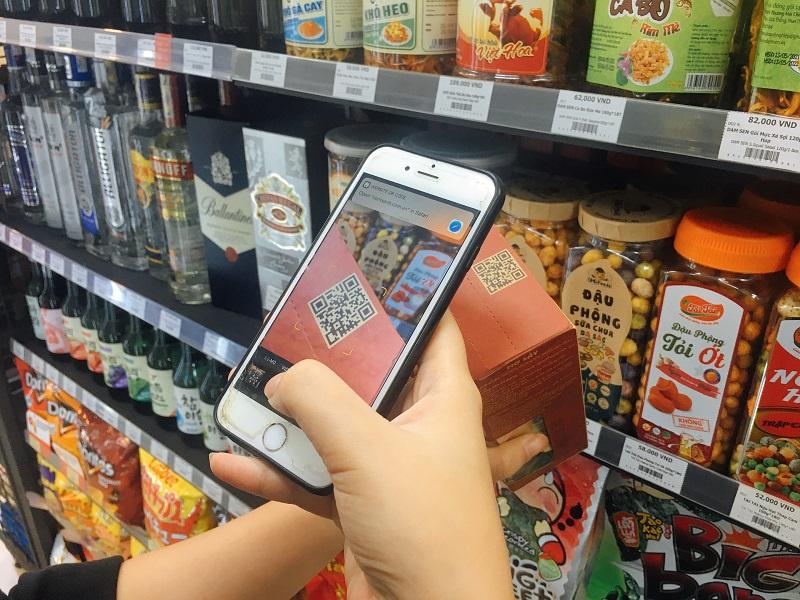 Người tiêu dùng quét mã QR trên sản phẩm với điện thoại thông minh. Ảnh: Mỹ Hạnh