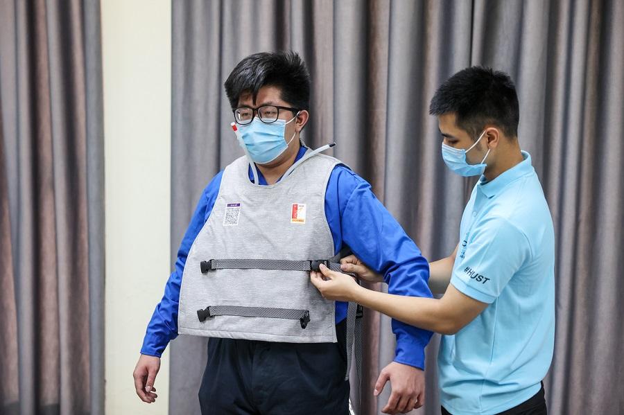 Phạm Đình Giỏi đang điều chỉnh áo làm mát cho phù hợp với người mặc. Ảnh: NVCC